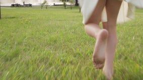 Γυμνά πόδια του μικρού κοριτσιού που τρέχουν στη χλόη στο θερινό πάρκο φιλμ μικρού μήκους