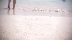 Γυμνά πόδια των τουριστών περαστικών που στηρίζονται σε μια τροπική αμμώδη παραλία 4k, απόθεμα βίντεο