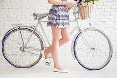 Γυμνά πόδια γυναικών κοντά στο άσπρο ποδήλατο Στοκ φωτογραφίες με δικαίωμα ελεύθερης χρήσης