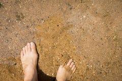 Γυμνή χαλάρωση ποδιών κοριτσιών στο σαφή ποταμό Στοκ Φωτογραφία
