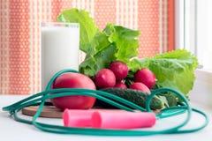 Γυμναστικά σχοινί και λαχανικά άλματος για μια υγιεινή διατροφή - η ντομάτα, το αγγούρι, το ραδίκι και το μαρούλι είναι στον πίνα στοκ φωτογραφίες