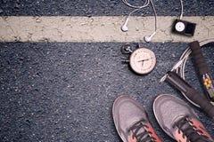 Γυμναστική ικανότητας και τρέχοντας εξοπλισμός Χρονόμετρο με διακόπτη και τρέχοντας παπούτσια, σχοινί άλματος και φορέας μουσικής Στοκ Φωτογραφίες