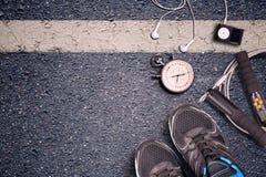 Γυμναστική ικανότητας και τρέχοντας εξοπλισμός Χρονόμετρο με διακόπτη και τρέχοντας παπούτσια, σχοινί άλματος και φορέας μουσικής Στοκ Φωτογραφία
