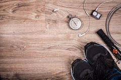 Γυμναστική ικανότητας και τρέχοντας εξοπλισμός Χρονόμετρο με διακόπτη και τρέχοντας παπούτσια, σχοινί άλματος και φορέας μουσικής Στοκ εικόνα με δικαίωμα ελεύθερης χρήσης