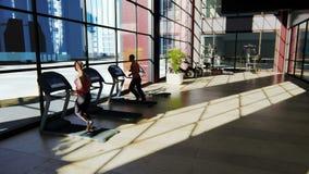 Γυμναστική με τις διάφορες μηχανές άσκησης σε το και τους ανθρώπους που περπατούν treadmill ελεύθερη απεικόνιση δικαιώματος