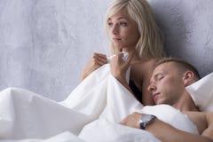 Γυμνοί άνδρας και γυναίκα στο κρεβάτι