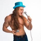 Γυμνόστηθος τραγουδιστών bodybuilder με μακρυμάλλη σε ένα μπλε καπέλο με ένα μικρόφωνο Στοκ εικόνα με δικαίωμα ελεύθερης χρήσης