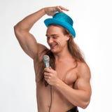Γυμνόστηθος τραγουδιστών bodybuilder με μακρυμάλλη σε ένα μπλε καπέλο με ένα μικρόφωνο Στοκ φωτογραφίες με δικαίωμα ελεύθερης χρήσης