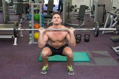 Γυμνόστηθος bodybuilder που ανυψώνει επάνω το μεγάλο βάρος barbell Στοκ Φωτογραφίες