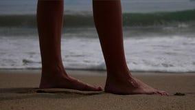 Γυμνό πόδι γυναικών που περπατά στη θερινή παραλία κλείστε επάνω το πόδι του νέου περπατήματος γυναικών κατά μήκος του κύματος το φιλμ μικρού μήκους
