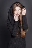 Γυναίκα Иeautiful με τα μακριά, πανέμορφα σκοτεινά ξανθά μαλλιά Είναι ντυμένη θερμό σε γκρίζο πλέκει το φόρεμα με μια κουκούλα Στοκ Φωτογραφίες