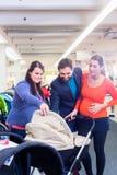Γυναίκα, άνδρας, και κυρία πωλήσεων στο κατάστημα μωρών Στοκ Εικόνες