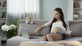 Γυναίκα έγκυος με το παιδί που εργάζεται στο lap-top, που κρατά τις γραφικές παραστάσεις, επιτυχής σταδιοδρομία απόθεμα βίντεο
