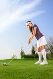 Γυναίκα έτοιμη να χτυπήσει τη σφαίρα γκολφ Στοκ Εικόνες