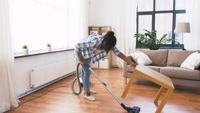 Γυναίκα ή νοικοκυρά με την ηλεκτρική σκούπα στο σπίτι απόθεμα βίντεο