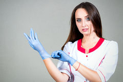 Γυναίκα ή νοσοκόμα ή γιατρός κοριτσιών στα ιατρικά χαμόγελα και το τέντωμα εσθήτων Στοκ φωτογραφία με δικαίωμα ελεύθερης χρήσης