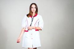 Γυναίκα ή νοσοκόμα ή γιατρός κοριτσιών στην ιατρική εσθήτα με το στηθοσκόπιο ο Στοκ φωτογραφία με δικαίωμα ελεύθερης χρήσης