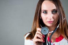 Γυναίκα ή νοσοκόμα ή γιατρός κοριτσιών στο ιατρικό στηθοσκόπιο ο χρήσεων εσθήτων Στοκ Εικόνα