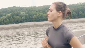 Γυναίκα αθλητών που τρέχει στο ανάχωμα στην κατάρτιση πρωινού υπαίθρια φιλμ μικρού μήκους