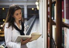 γυναίκα ανάγνωσης ραφιών στοκ φωτογραφία με δικαίωμα ελεύθερης χρήσης