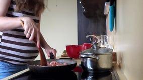 Γυναίκα αναμενουσών μητέρων που προετοιμάζει το κρέας στο μαγείρεμα του τηγανιού Μεγάλη θηλυκή κοιλιά απόθεμα βίντεο