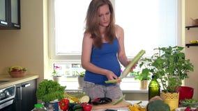 Γυναίκα αναμενουσών μητέρων που χρησιμοποιεί έναν υπολογιστή ταμπλετών για να προετοιμάσει τη σαλάτα λαχανικών απόθεμα βίντεο