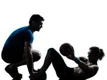 Γυναίκα ανδρών που ασκεί τη σκιαγραφία σφαιρών ικανότητας βαρών workout Στοκ Φωτογραφία