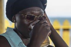 Γυναίκα από την μπύρα κατανάλωσης της Άκρα σε έναν φραγμό σε Takoradi στοκ φωτογραφία