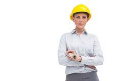 Γυναίκα αρχιτεκτόνων με το κίτρινο κράνος και το κυλημένο επάνω σχέδιο Στοκ εικόνα με δικαίωμα ελεύθερης χρήσης