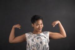 Γυναίκα αφροαμερικάνων με τα ισχυρά όπλα στο υπόβαθρο πινάκων Στοκ εικόνα με δικαίωμα ελεύθερης χρήσης