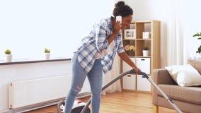 Γυναίκα αφροαμερικάνων με την ηλεκτρική σκούπα στο σπίτι απόθεμα βίντεο