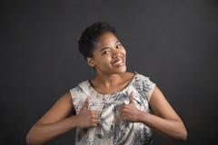 Γυναίκα αφροαμερικάνων με τους αντίχειρες επάνω στο σήμα χεριών στο υπόβαθρο πινάκων Στοκ φωτογραφία με δικαίωμα ελεύθερης χρήσης