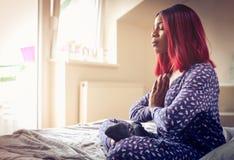 Γυναίκα αφροαμερικάνων που έχει την περισυλλογή στο κρεβάτι στο πρωί στοκ φωτογραφία με δικαίωμα ελεύθερης χρήσης