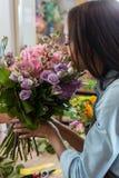 Γυναίκα αφροαμερικάνων που μυρίζει τα όμορφα λουλούδια στο ανθοπωλείο Στοκ Εικόνες