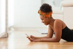 Γυναίκα αφροαμερικάνων που στέλνει ένα μήνυμα κειμένου σε ένα κινητό τηλέφωνο Στοκ Εικόνα
