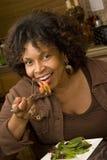 Γυναίκα αφροαμερικάνων που χαμογελά τρώγοντας μια σαλάτα Στοκ Φωτογραφίες