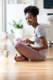 Γυναίκα αφροαμερικάνων που χρησιμοποιεί ένα lap-top στο καθιστικό της - ο Μαύρος Στοκ φωτογραφία με δικαίωμα ελεύθερης χρήσης