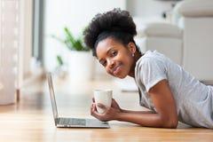 Γυναίκα αφροαμερικάνων που χρησιμοποιεί ένα lap-top στο καθιστικό της - ο Μαύρος Στοκ Φωτογραφίες