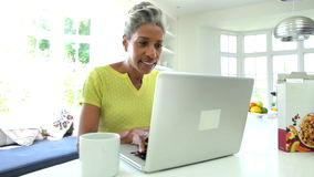 Γυναίκα αφροαμερικάνων που χρησιμοποιεί το lap-top στην κουζίνα στο σπίτι απόθεμα βίντεο