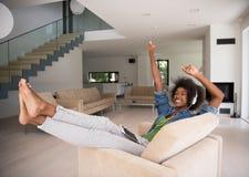 Γυναίκα αφροαμερικάνων στο σπίτι στην καρέκλα με την ταμπλέτα και το επικεφαλής pho Στοκ Εικόνες