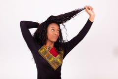 Γυναίκα αφροαμερικάνων σχετικά με τις σγουρές τρίχες της στοκ φωτογραφίες