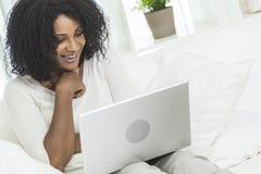 Γυναίκα αφροαμερικάνων, φορητός προσωπικός υπολογιστής στο σπίτι Στοκ Εικόνες