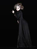 Γυναίκα βαμπίρ με το μαύρο γοτθικό κοστούμι αποκριές Στοκ Εικόνες