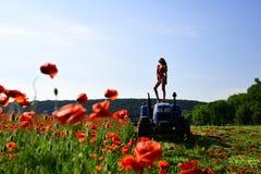 Γυναίκα γεωπόνων στο τρακτέρ, λουλούδι παπαρουνών στοκ εικόνες