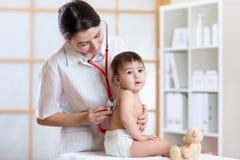 Γυναίκα γιατρών που εξετάζει τους πνεύμονες του παιδιού με το στηθοσκόπιο στοκ φωτογραφία με δικαίωμα ελεύθερης χρήσης