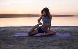 Γυναίκα γιόγκας στην παραλία στο ηλιοβασίλεμα Στοκ Φωτογραφίες