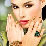 Γυναίκα γοητείας με τα όμορφα χρυσά καρφιά και το σμαραγδένιο δαχτυλίδι Στοκ Φωτογραφίες