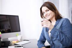 Γυναίκα γραφείων με το ποτήρι του νερού που κλίνει στο γραφείο Στοκ εικόνες με δικαίωμα ελεύθερης χρήσης