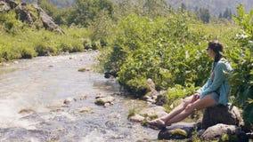 Γυναίκα γυναικών τουριστών που στηρίζεται στην ακτή ποταμών και που κοιτάζει στο ρέοντας νερό απόθεμα βίντεο