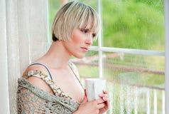 Γυναίκα δίπλα στο παράθυρο το πρωί στοκ φωτογραφίες